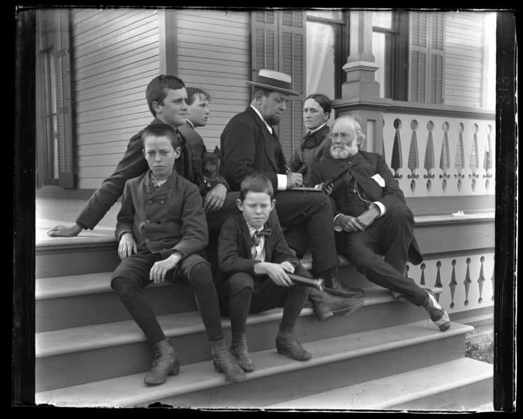 A group of seven sit on the porch staircase, posed.