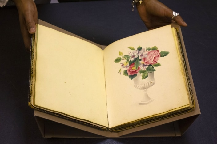 Jasmine Smith, LCP African American history subject specialist, holds a rare friendship album.