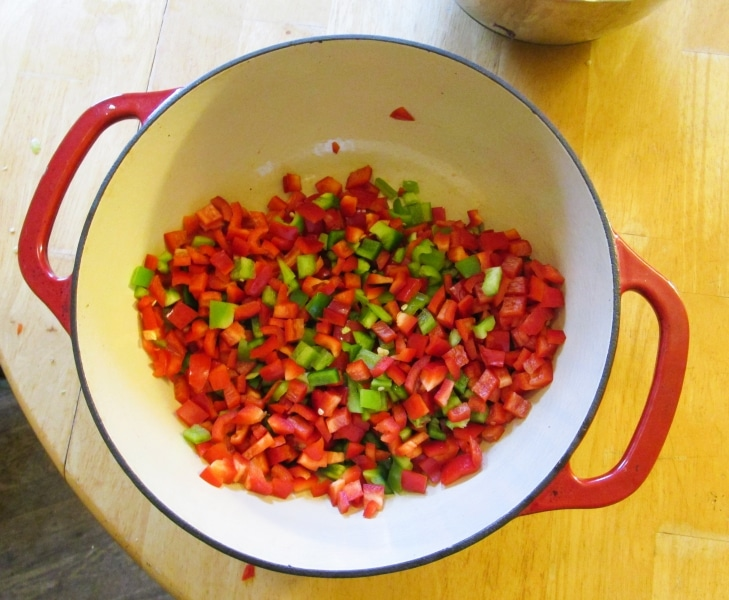 Minced red and green peppers in an cast iron enamel pot