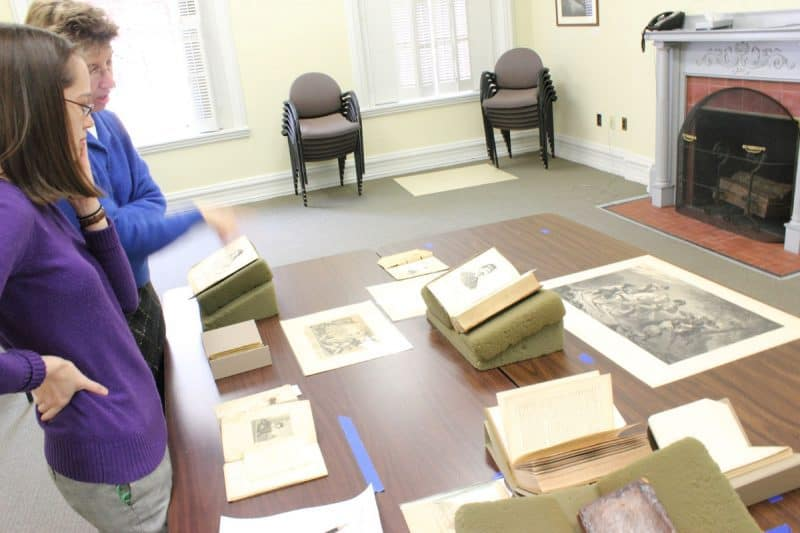 Linda August and Sarah Weatherwax at work laying out exhibition cases.