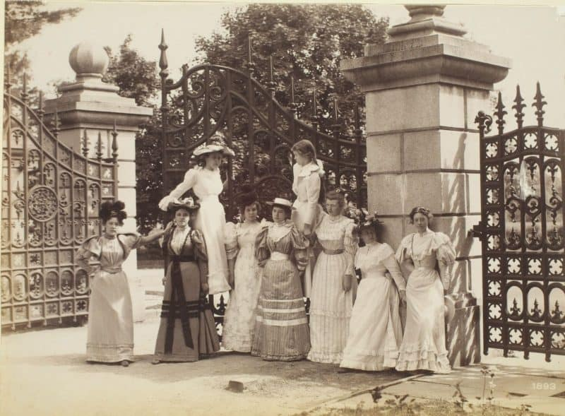 Group of well-dressed women posed before a large gate.
