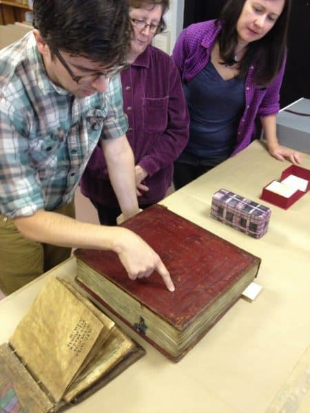 Three people inspect the bindings of a large, red book.