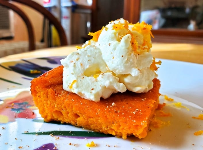 Carrot pudding served with nutmeg, orange zest, and whipped cream
