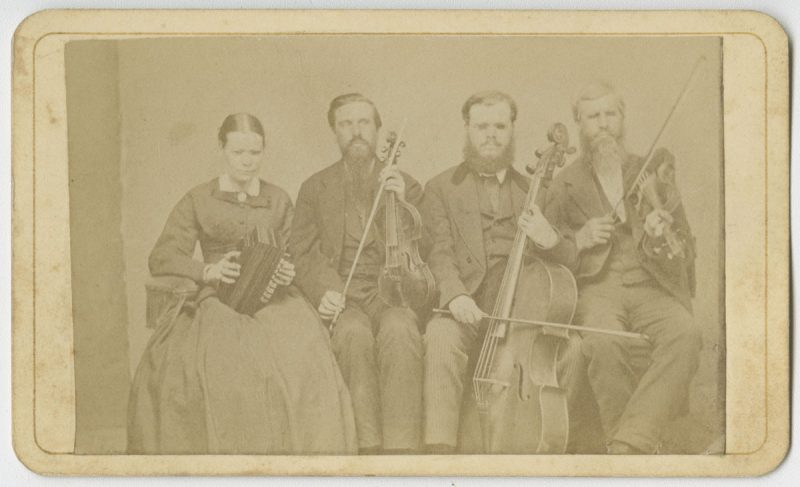 Picture shows one woman and three men, seated next to each other, and holding instruments. The woman holds an accordion in her lap and she looks slightly down. To her left is a man, his eyes closed, who holds a viola perpendicular to his lap with one hand and a bow in his other. To his left is a man resting a cello between his legs. He holds a bow across the base of the cello with his right hand. To his left is the last man, his eyes closed, who holds a violin by his left shoulder and a raised bow in in his right hand. The woman, as well as the man who holds a cello, wear glasses. The woman wears a dark dash colored corseted dress with long sleeves and a long skirt. The men, who look toward the viewer, are bearded and wear dark dash colored suits.  [End of description]