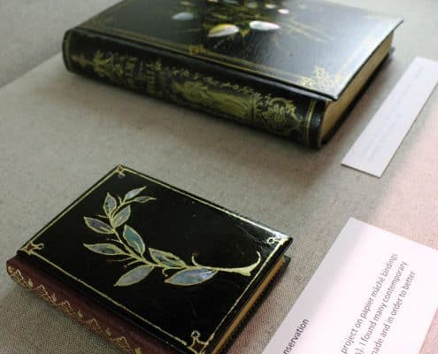 Two examples of papier-mâché bindings laid out in an exhibition case, 2010. Jennifer Rosner, Chief of Conservation.