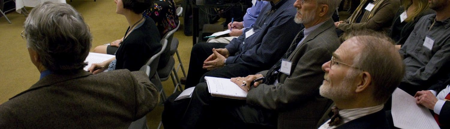 Photograph depicting a crowd of attendees sitting and watching a presentation.